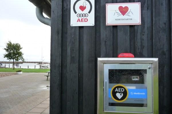 Mit gut sichtbaren Hinweisschildern versehener Defibrillator in einem dänischen Hafen.