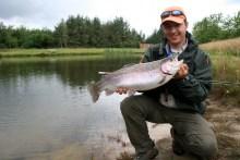 Angler mit Regenbogenforelle